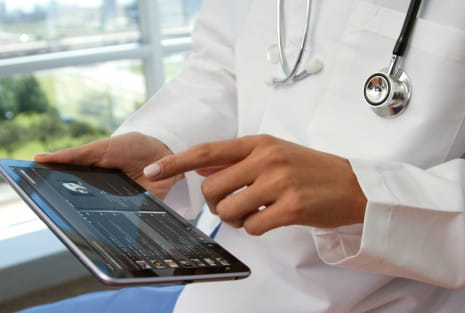 doctor holding a tablet with a healthcare app